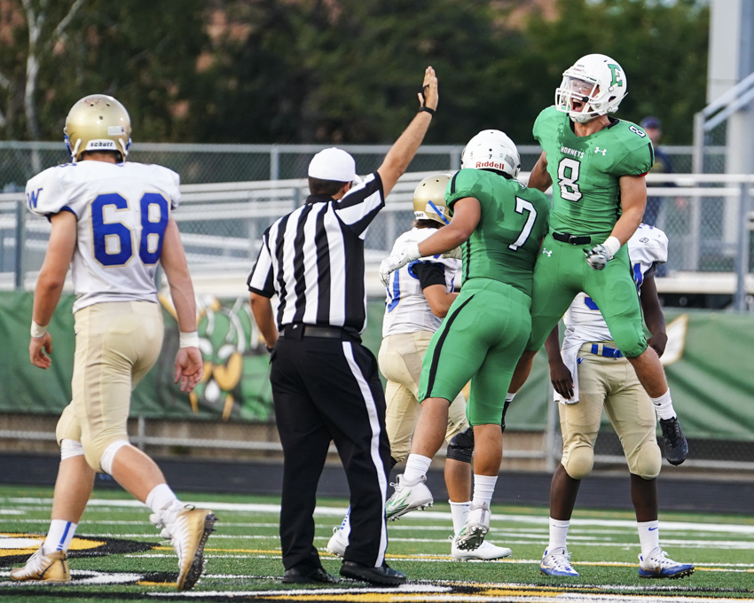 Hornets Senior Captain Nicholas Bloom (8) and Senior Dylan Hoye (7) celebrate an early first half defensive three and out stop in the 29-0 victory over Wayzata. Photo by Travis Ellison, SportsEngine