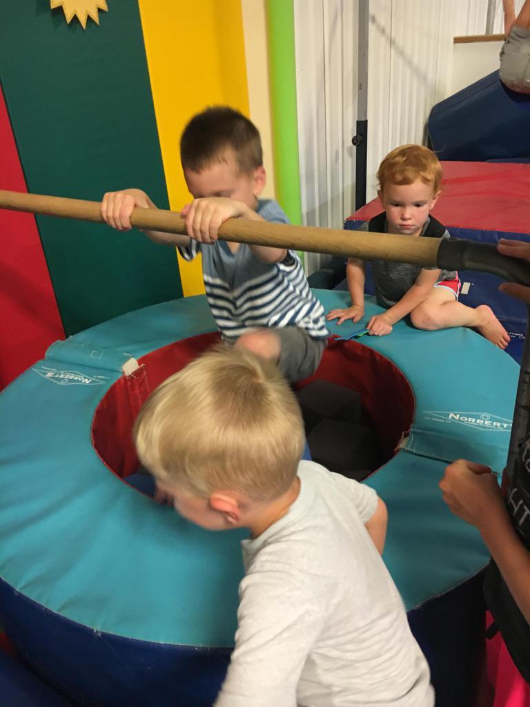 Preschool gymnasts climbing on equipment