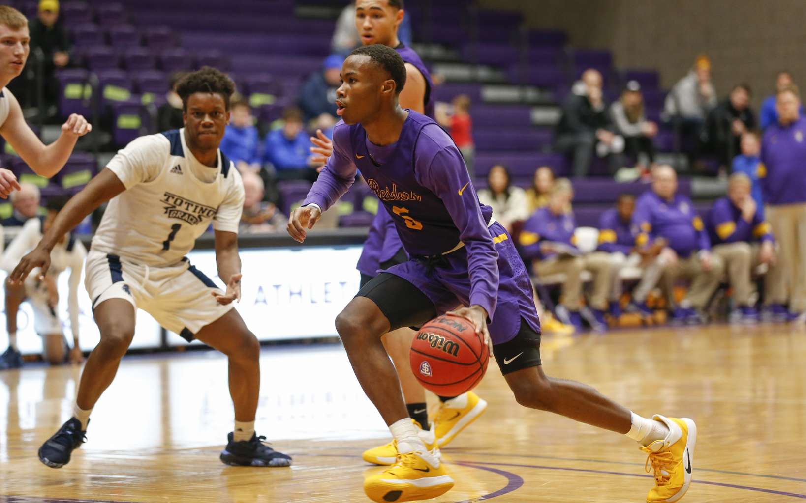 Cretin-Derham Hall's Tre Holloman (5) dashes down the lane against Totino-Grace Saturday night. The Raiders defeated the Eagles 64-54 at the University of St. Thomas. Photo by Jeff Lawler, SportsEngine