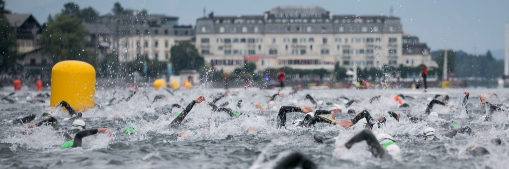 IRONMAN 70.3 Zell am See-Kaprun athletes swimming in lake Zell with the water splashing around