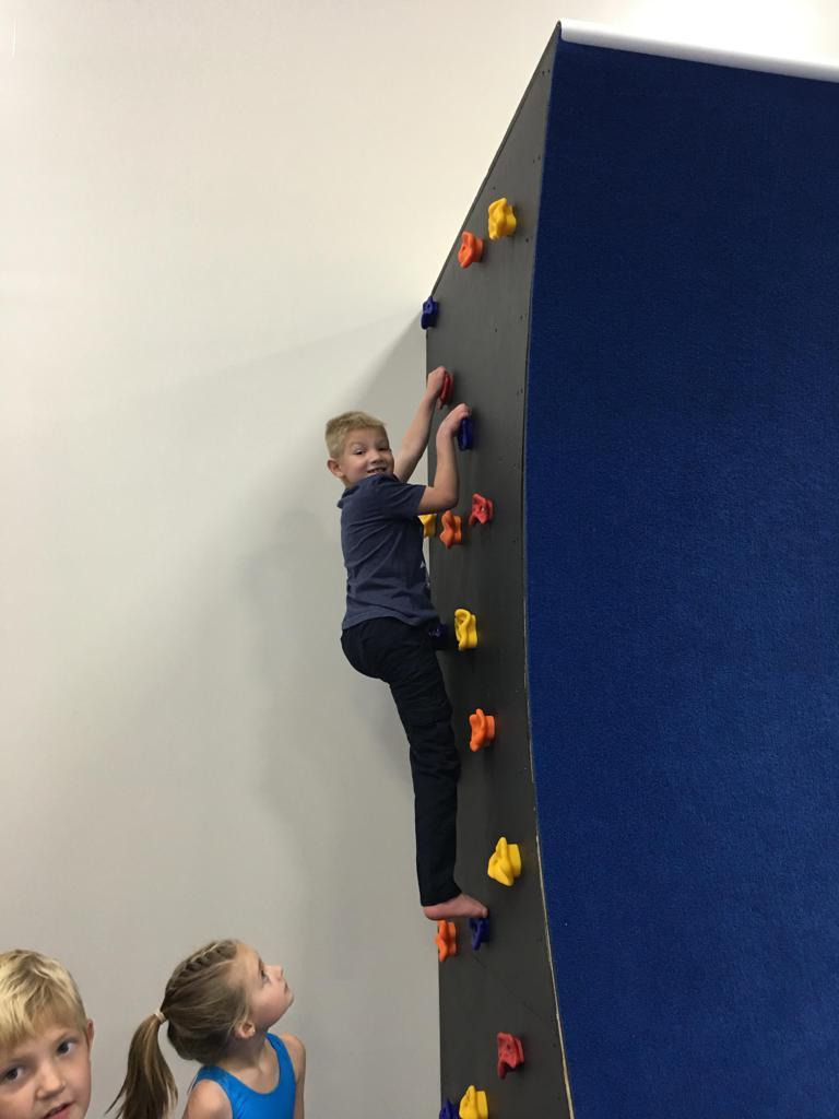 Children climbing Ninja Zone rock wall at Jam Hops birthday party