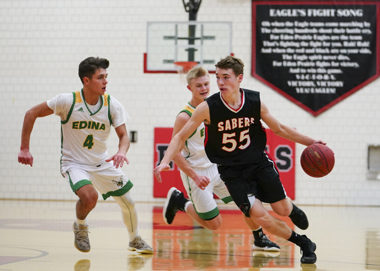 Shakopee sophomore guard Will Cordes (55) drives past Edina senior guard Anders Nelson (4) on his way to the basket late in the second half as Shakopee falls to Edina 74-66. Photo by Travis Ellison, SportsEngine