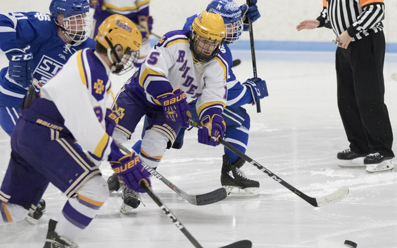 Cretin-Derham Hall sophomore Matthew Gleason battles two St. Thomas Academy defenders for the puck Wednesday night in St. Paul. The Raiders came up short against the Cadets 2-0 in a battle of top-5 ranked Class 2A teams. Photo by Jeff Lawler, SportsEngine