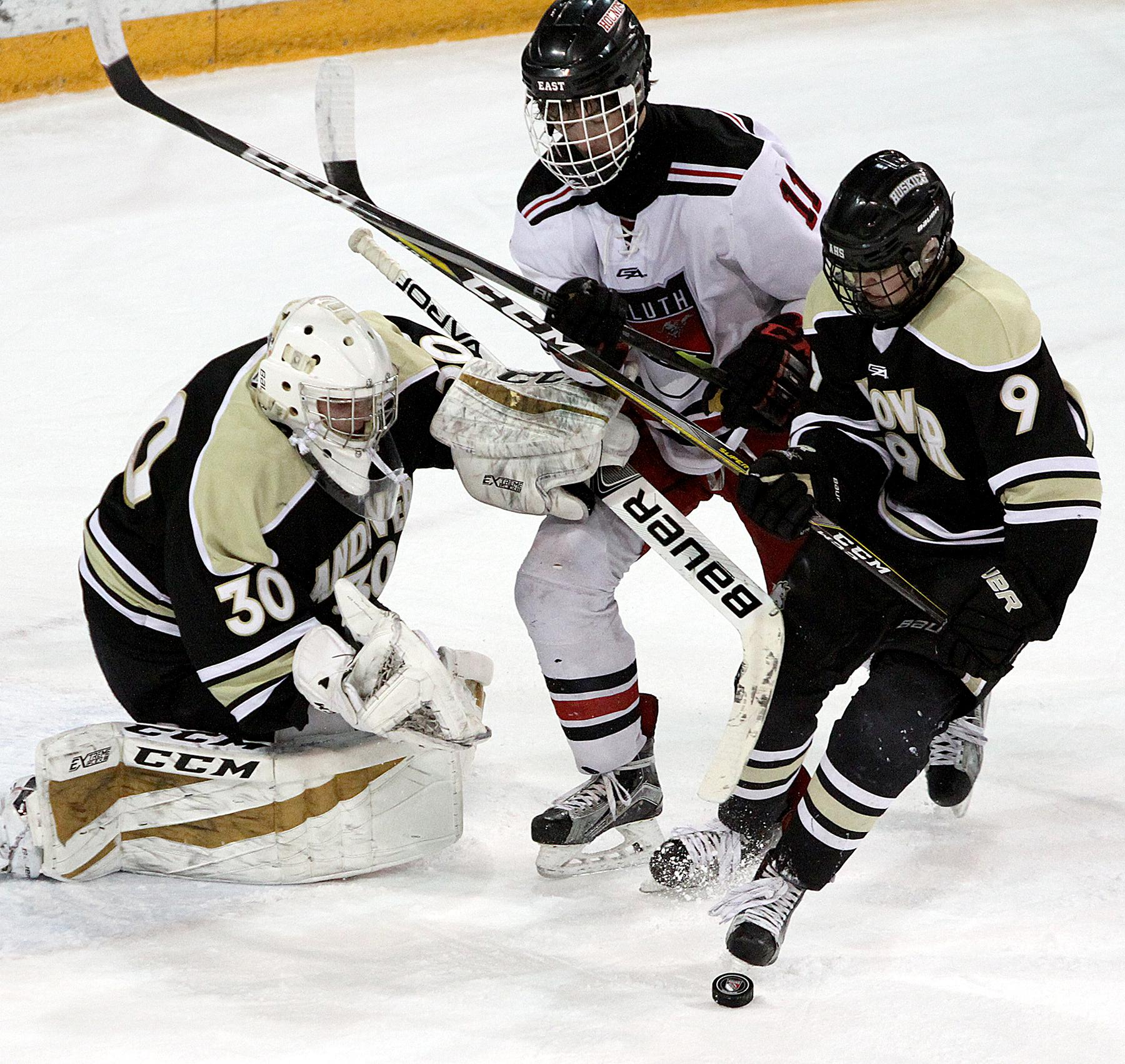 Duluth East's Nick Lanigan fights for a rebound between Andover goalie Ben Fritsinger and defenseman Eric Chartier late in the first period Thursday at AMSOIL Arena in Duluth. Photo by Drew Herron, SportsEngine