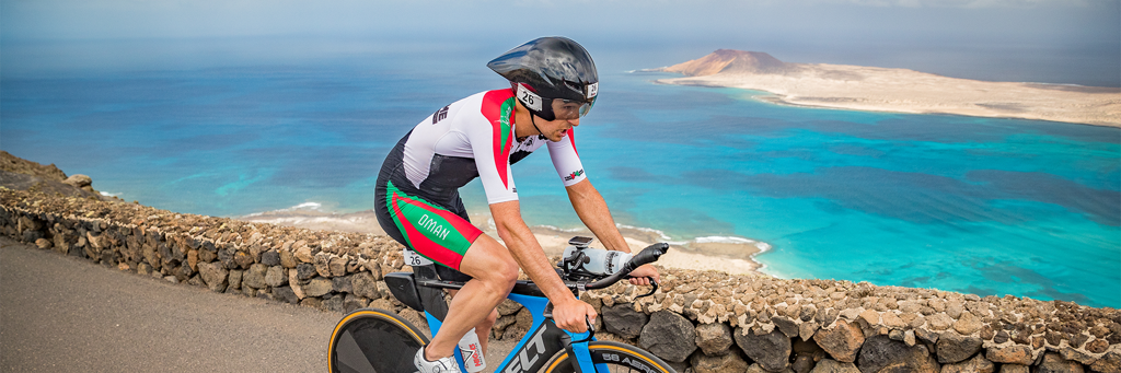 Athlete biking near the shore of turquoise water at Lanzarote