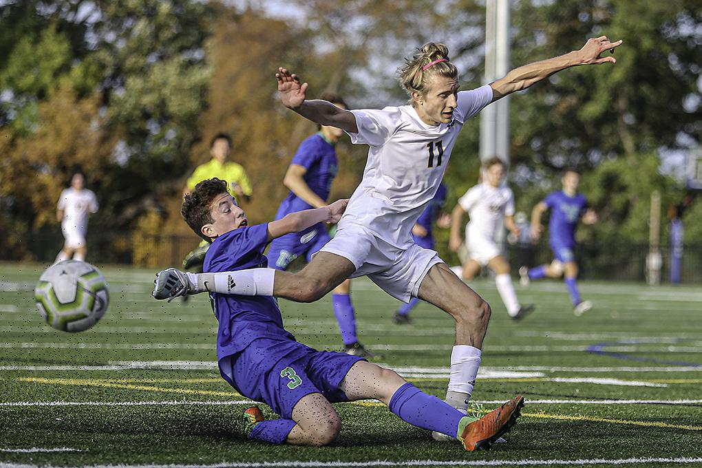 Breck senior Spencer Chapman (11) is upended by Blake defender Jonah Halper (3) on his way to the goal in the first half. Breck scored three times in the game's last 15 minutes to win 4-1. Photo by Mark Hvidsten, SportsEngine
