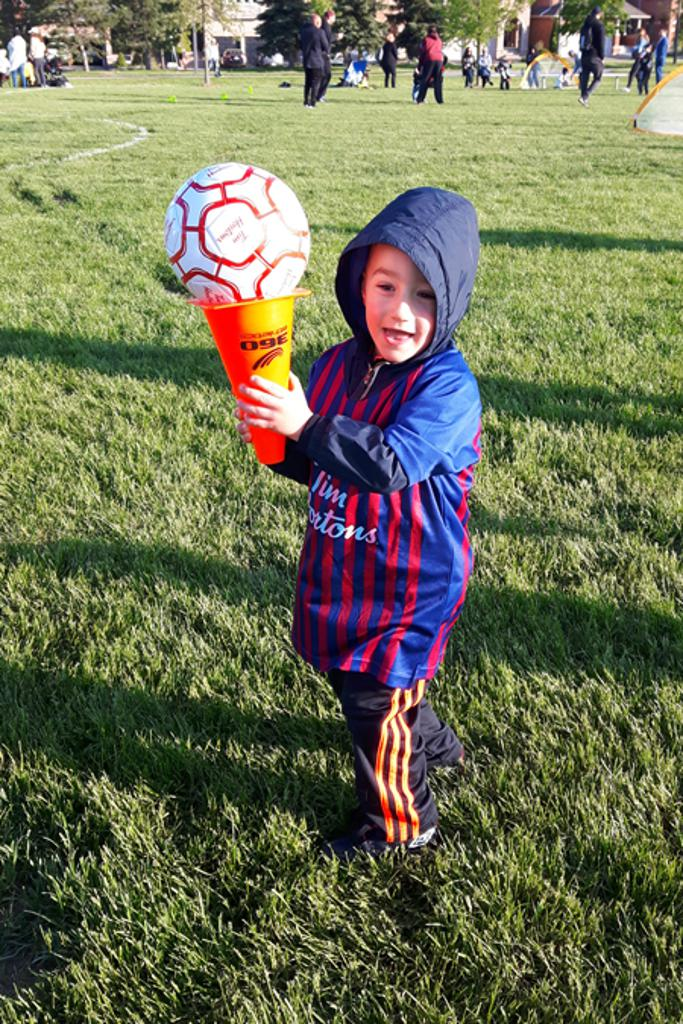 young boy with pylon and soccer ball for the first time