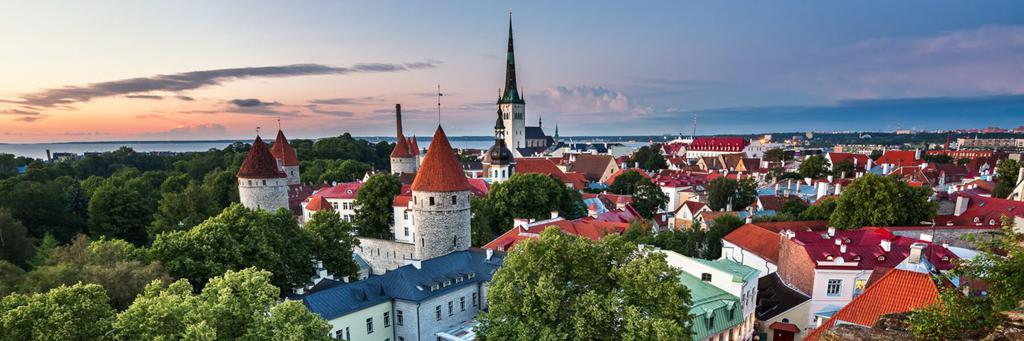 Scenic view of Tallinn's Old Town with Olaf's church and Walls of Tallinn next to more buildings and views of parks and the sea