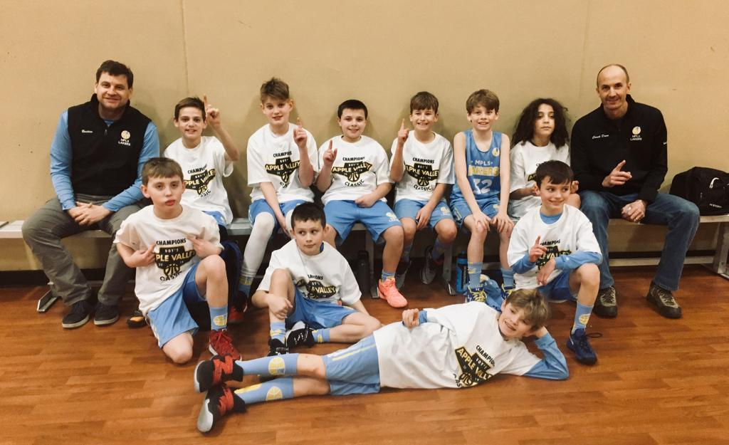 Minneapolis Lakers Boys 5th Grade White pose with their T-Shirts after becoming the Champions at Apple Valley Classic in Apple Valley, MN