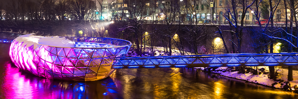 An illuminated Murinsel in the shape of an giant sea shell in the Mur river in Graz at night