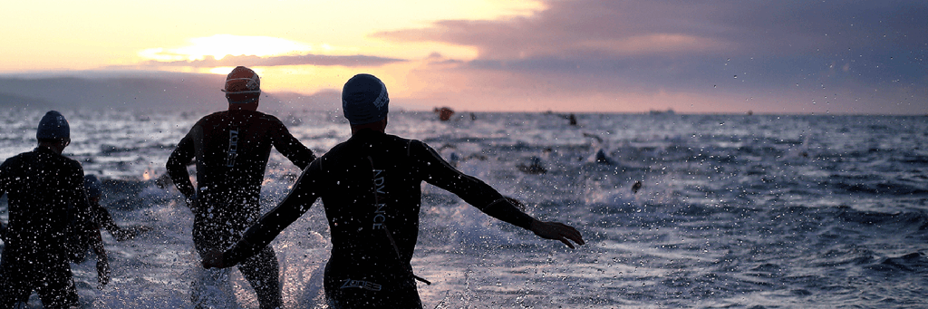Athletes in Weymouth Bay at early sunrise ready to start the swim at IRONMAN 70.3 Weymouth