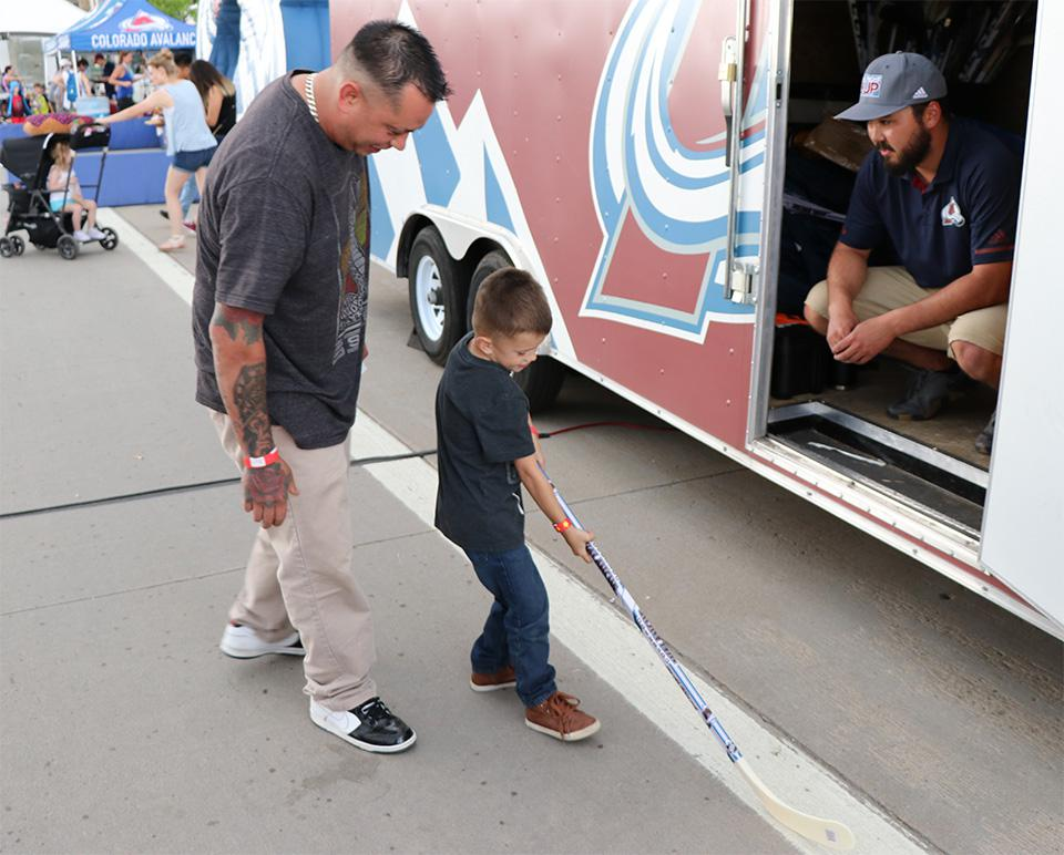 A child receives a free street hockey stick and ball handed out by the Colorado Avalanche through their Game On initiative at the Colorado State Fair in late August. Photo courtesy of the Colorado Avalanche