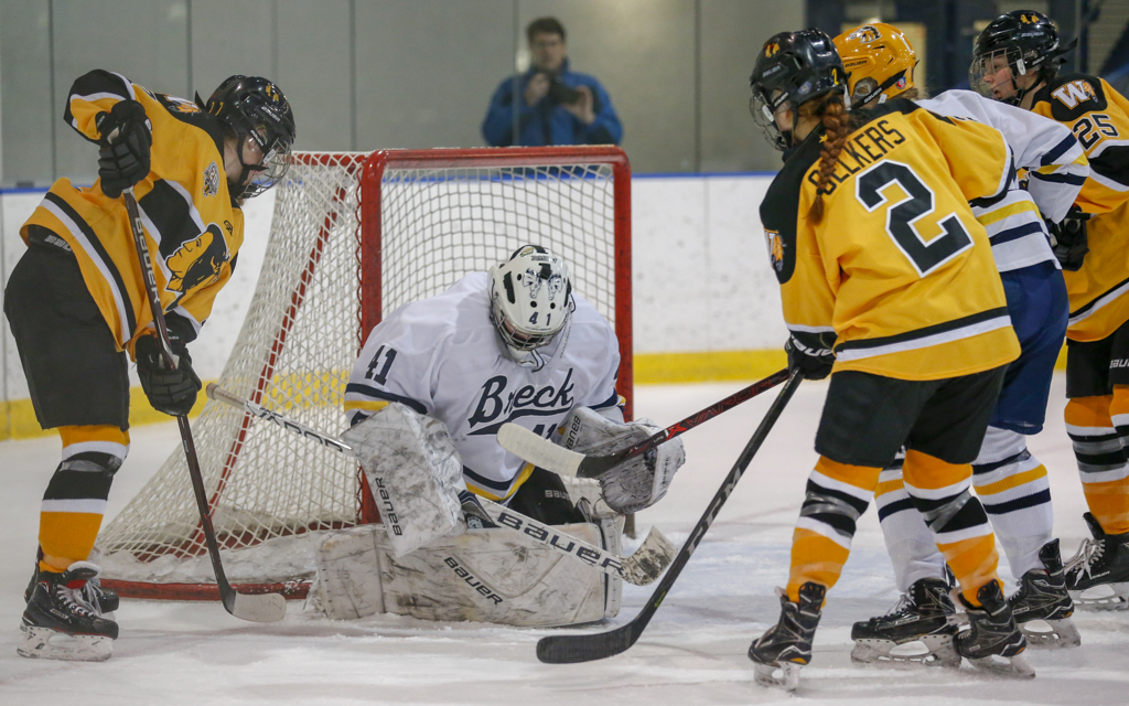 With a crowd around the net, Breck goalie Uma Corniea makes a save against Warroad. Corniea stopped 40 of 43 shots in the Mustang's 3-0 loss to the Warriors. Photo by Jeff Lawler, SportsEngine