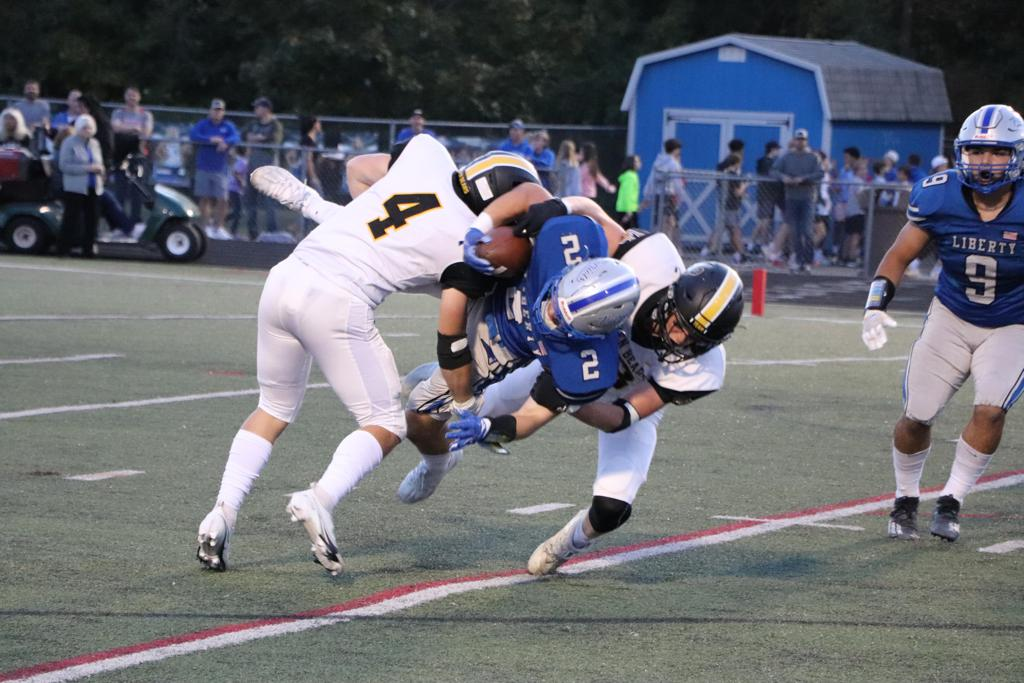 Upper Arlington defensive back Doak Buttermore assists in bringing down Olentangy Liberty receiver Tyler Greer in the backfield.