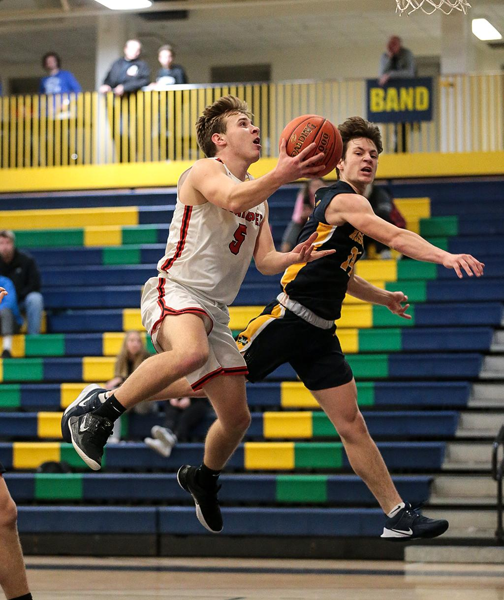 Shakopee's Caleb Druvenga (5) lays the ball up for two of his 15 points on Friday night. The Sabers took an early lead and eased past South Suburban Conference rival Rosemount for an 84-71 win. Photo by Cheryl A. Myers, SportsEngine