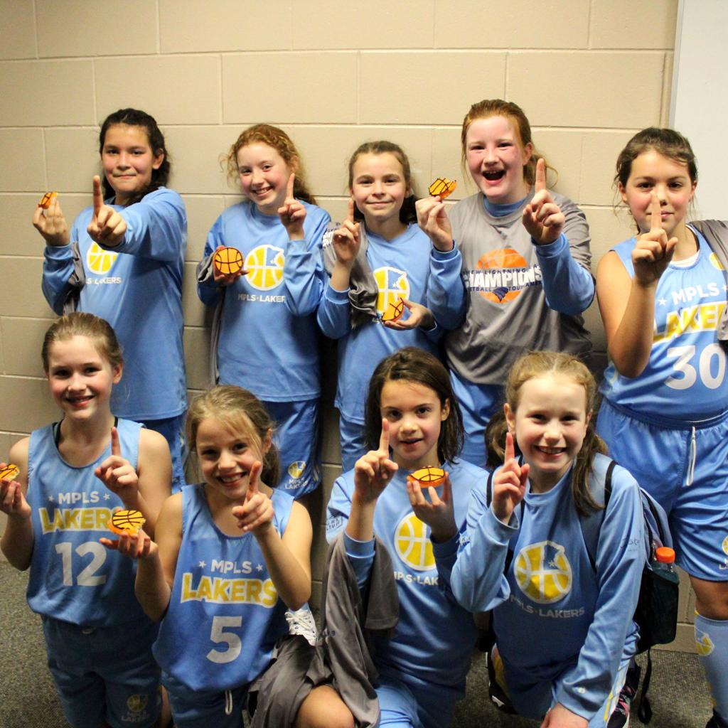 Minneapolis Lakers Girls 5th Grade Gold pose with their t-shirts and cookie after taking 1st at Eastview