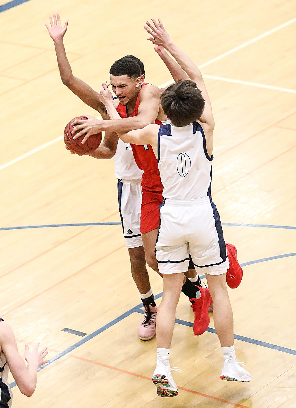 Jalen Suggs gets caught between two defenders. Despite the double-team effort, Suggs scored 18 points helping the Redhawks earn another trip to next week's Class 2A state tournament. Photo by Cheryl Myers, SportsEngine