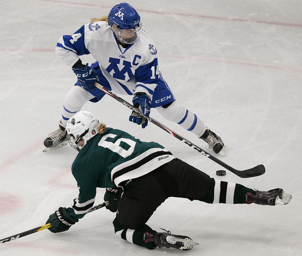 Minnetonka senior defender Maggie Nicholson (14) takes the puck away from Kayla Santl (6). The Skippers scored three goals in the first period and cruised to an 8-0 win over Roseau. Photo by Cheryl A. Myers, SportsEngine