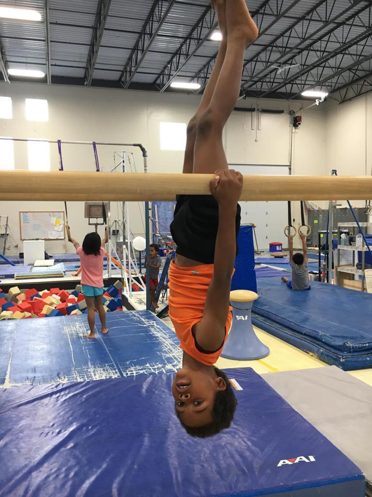 Boy gymnast hanging upside-down on parallel bars