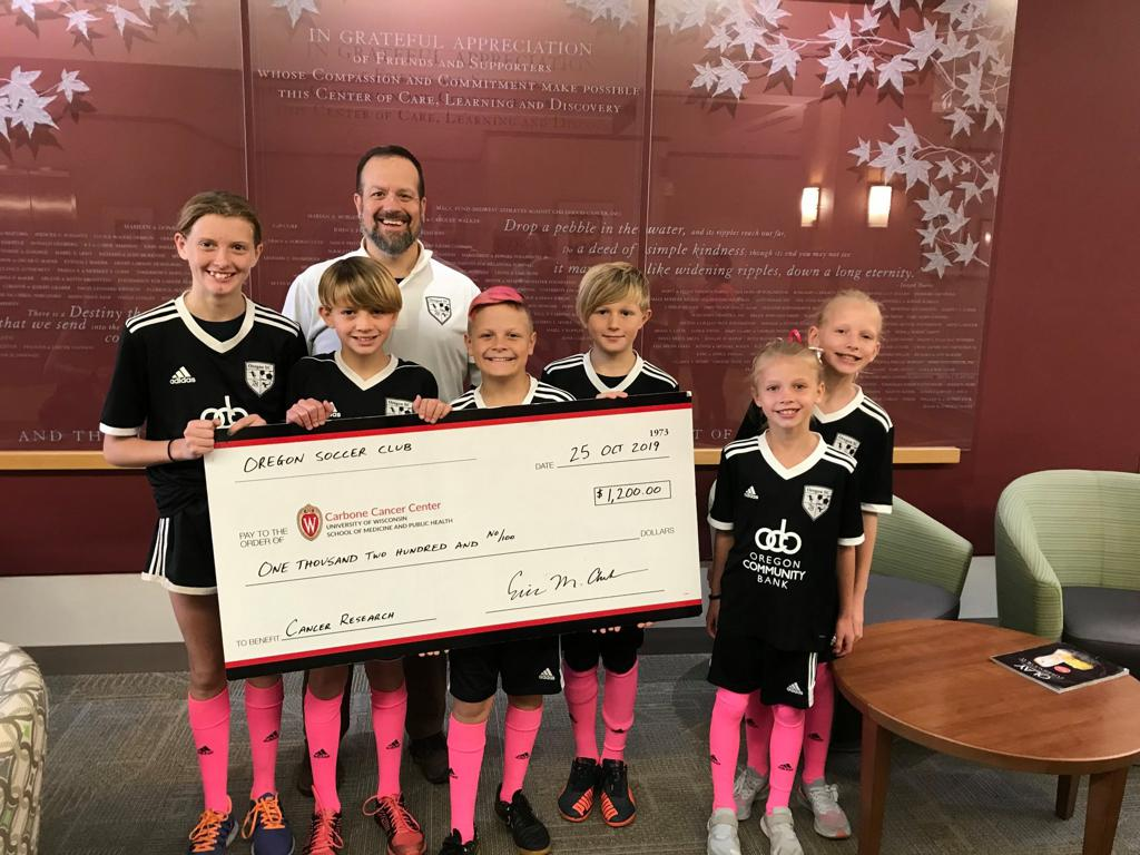 Oregon SC players Alex, Kaleb and Tra Schmidt, McKinley and Nora Younggren and Barrett Anderson presented a check for $1,200 to the UW Carbone Cancer Center for cancer research following the club's charity for the 2018-19 season.