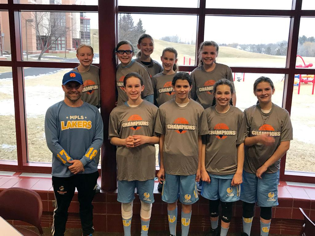 Minneapolis Lakers Girls 6th Grade Gold pose with their Championship t-shirts after taking 1st at the Eastview Girls Basketball Tournament in Apple Valley, MN