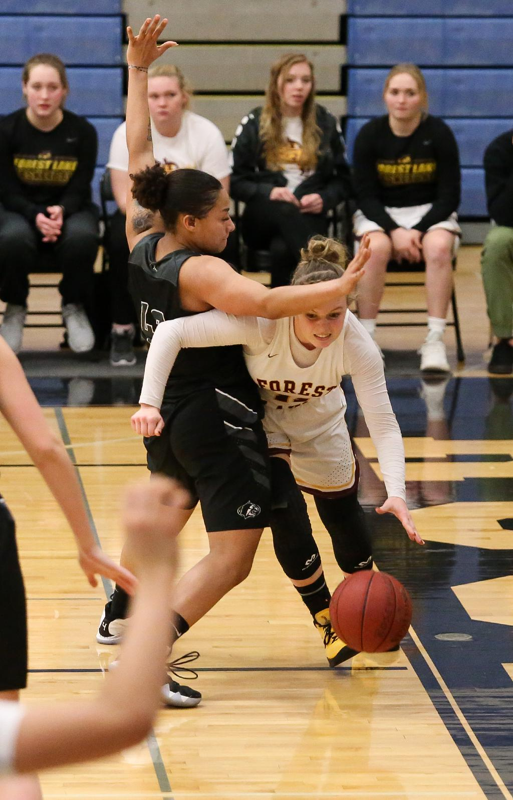 Lexie Hultman (11) forces her way past Jada Hood along the baseline. Hultman led the Rangers' scoring with 10 points in a 52-47 loss at Roseville High School. Photo by Cheryl Myers, SportsEngine