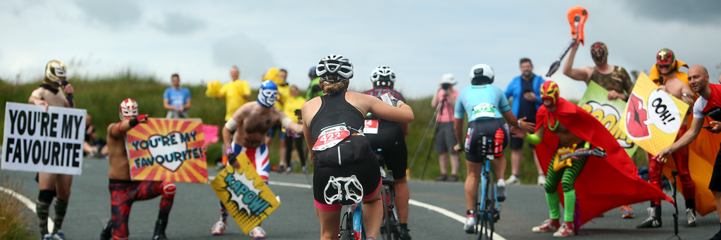 Athletes who are biking up a hill are motivated and supported by masked people carrying posters at IRONMAN UK