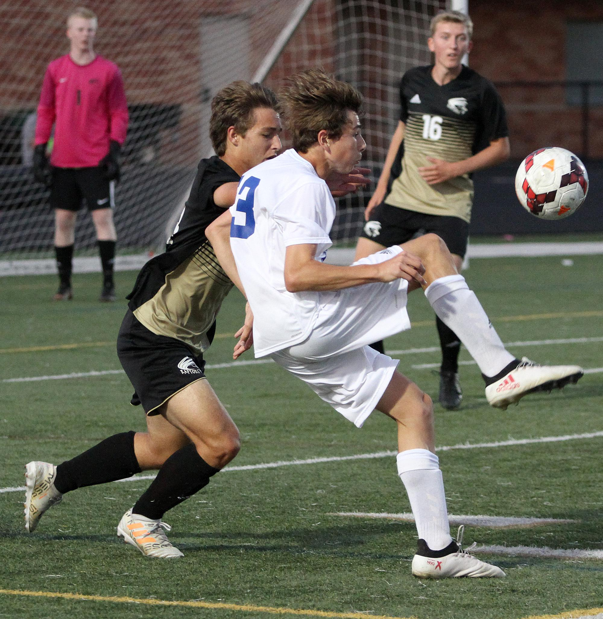 East Ridge junior defender Chris Duliere marks Woodbury sophomore attacker Devin Padelford late in the first half Tuesday night at East Ridge High School. The host Raptors beat Woodbury 2-1. Photo by Drew Herron, SportsEngine