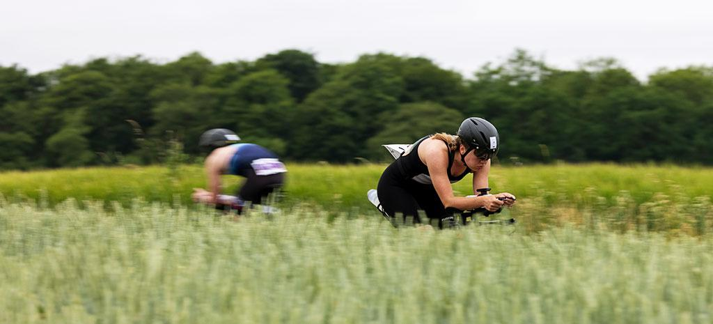 IRONMAN 70.3 European Championship Elsinore athletes are biking in the Danish countryside while passing the woods