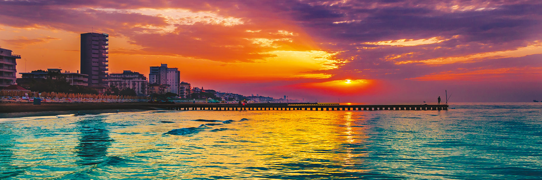 People on a pier on the beach in Jesolo at sunset, the colors the sky red and is reflected in the Mediterranean Sea