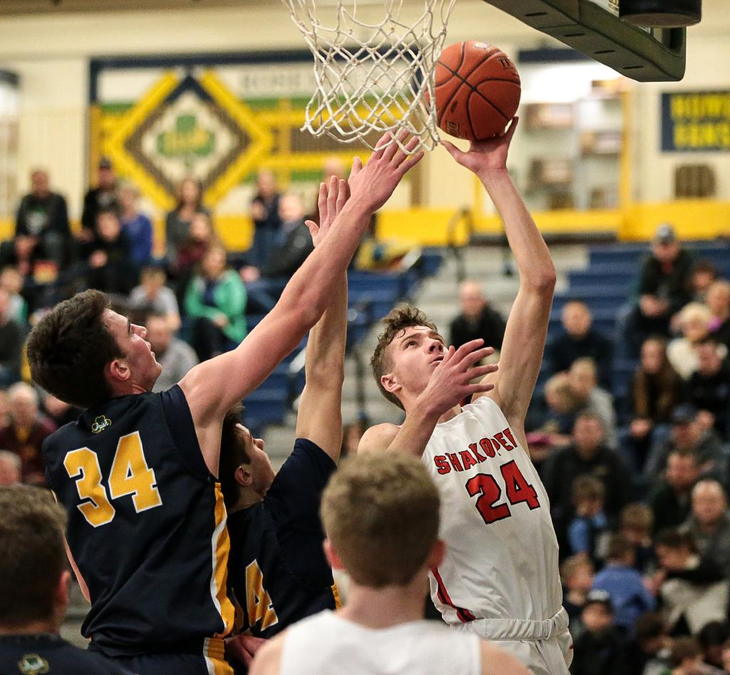 Shakopee's Charlie Katona (24) puts the ball up past two Rosemount defenders. Katona's game-high 35 points led the Sabers to an 84-71 win over the Irish on Friday night. Photo by Cheryl A. Myers, SportsEngine