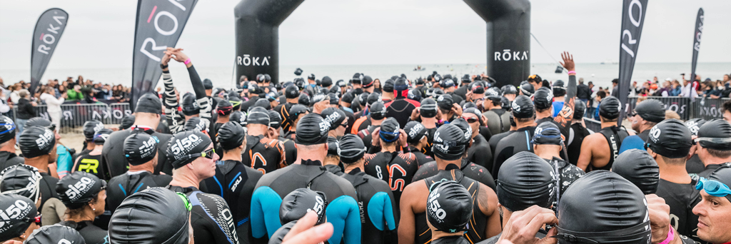 Overview of 5150 Cervia athletes with black swim caps under the start arch ready to take on the swim in the Adriatic Sea