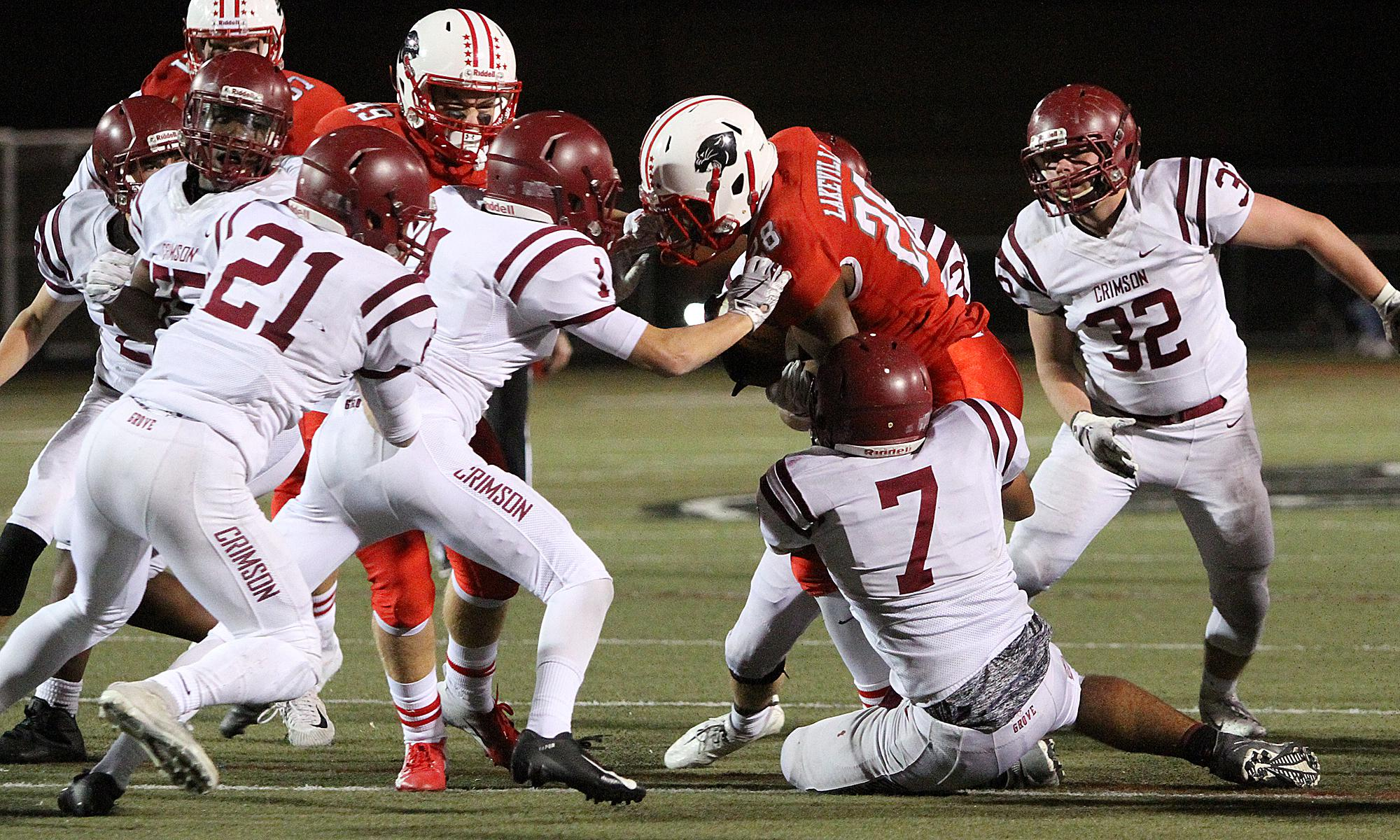 Lakeville North senior running back Brian Curtis Jr. is met at the line of scrimmage late in the first half by a group of Maple Grove defenders, including Anthony Gipson (7) and Aaron Tollefson (11). Photo by Drew Herron, SportsEngine