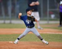 Young baseball pitcher in wind up about to through the ball