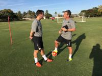 Buckle and Head Assistant Coach Adam Smith discuss training during one of the club's workout sessions.