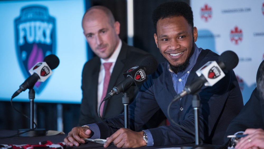 Julian de Guzman, sitting beside Paul Dalglish and smiling after a question from a journalist, while his press conference announcing his retirement