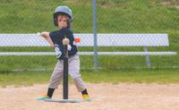 Kid hitting ball on t ball stand