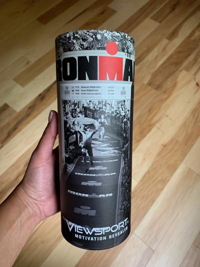 A tube that's wrapped in an IRONMAN finish line scene, was mailed with tank inside