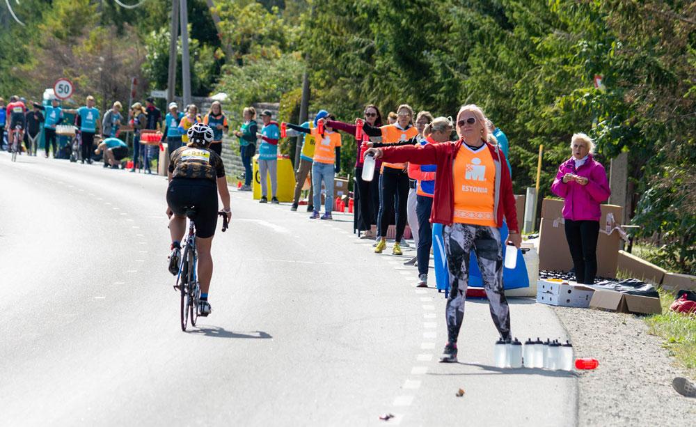 Volunteers geben Wasser an Athleten aus beim IRONMAN Tallinn
